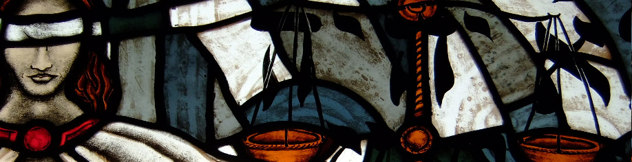 Stained glass image of blindfolded Justicia holding a sword and scale